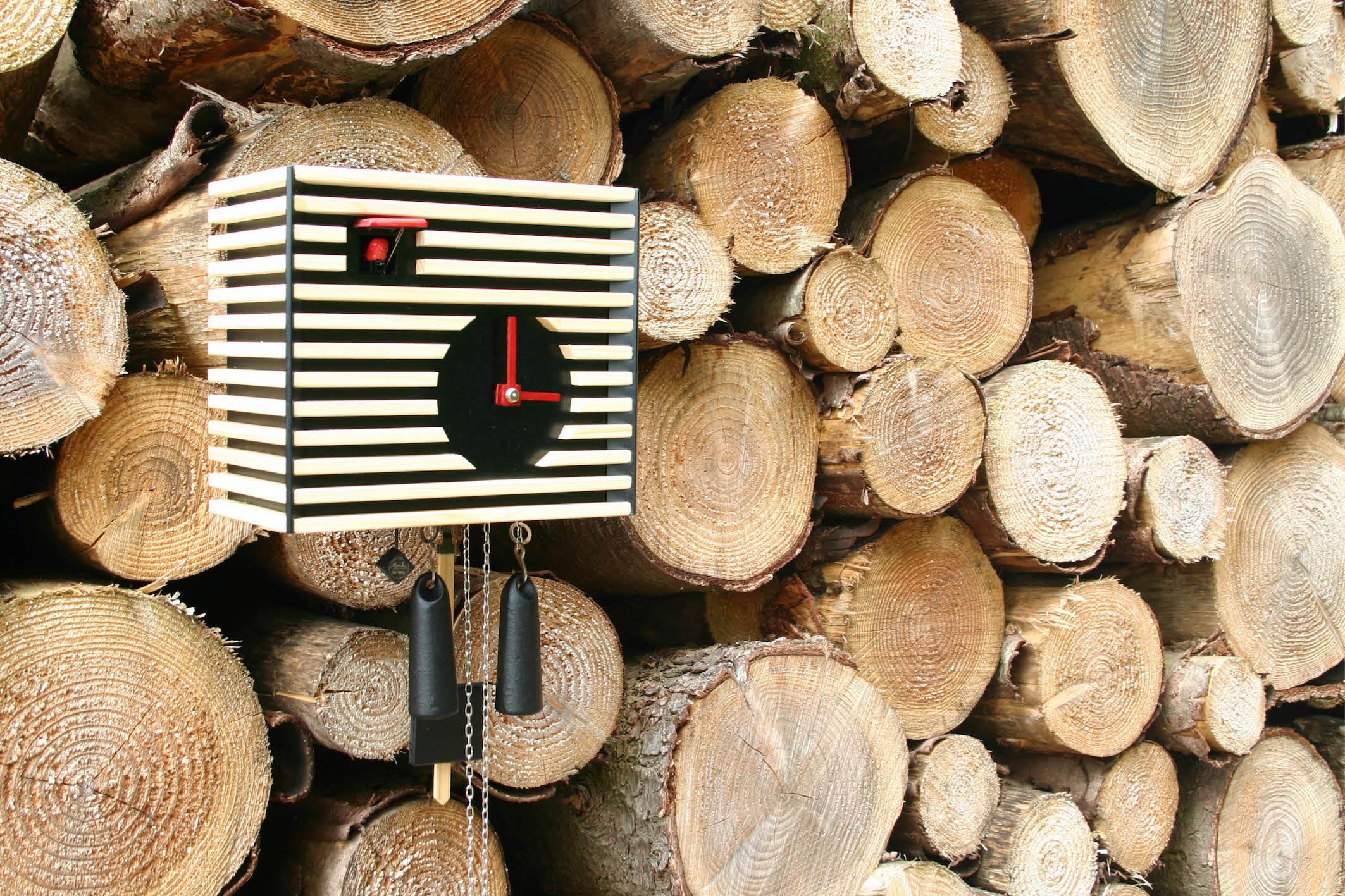 Kuckucksuhr an Holzbeige